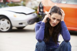 Motor Vehicle Accident female in front of car accident on the phone hand on head 300x200